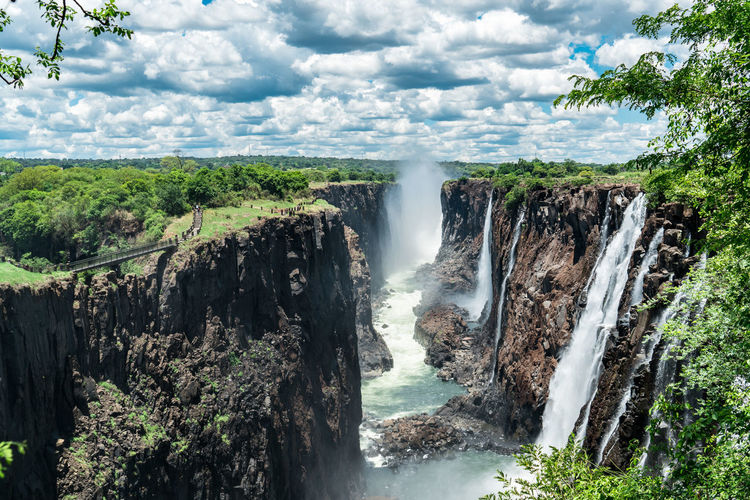 Mighty Victoria Falls with clouds of thunder. Water is falling and rises up again on the wind. A thunderous place to marvel about the sounds, views and all its powers. The Zambezi will continue its journey to the ocean while I'll keep staring into the distance. Livingstone  Zambia Zimbabwe Africa Beauty In Nature Cliff Cloud - Sky Day Flowing Water Forest Long Exposure Motion Nature No People Outdoors Power In Nature Scenics Sky Splashing Tree Victoria Falls Water Waterfall