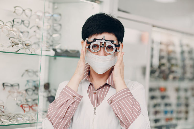Portrait of woman holding optometry equipment at store
