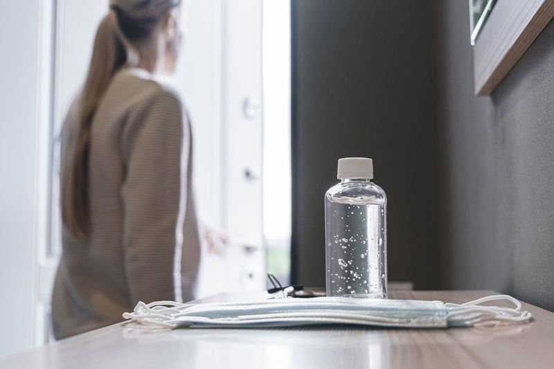 Midsection of woman standing by table at home
