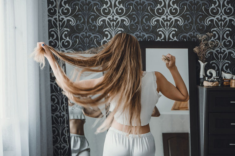 Rear view of woman looking at mirror while holding hair