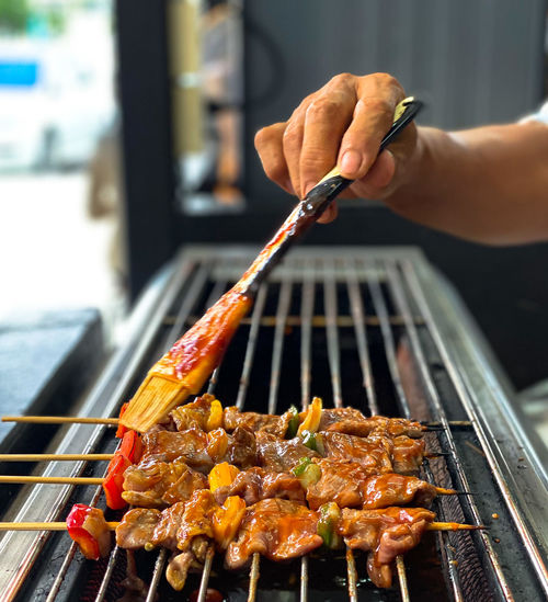 Cropped image of person preparing food on barbecue grill