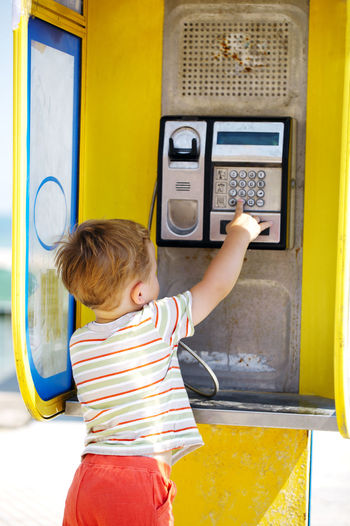 Rear view of boy standing at telephone booth