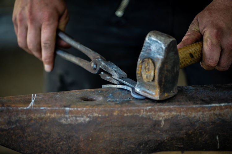 Midsection of man working on metal
