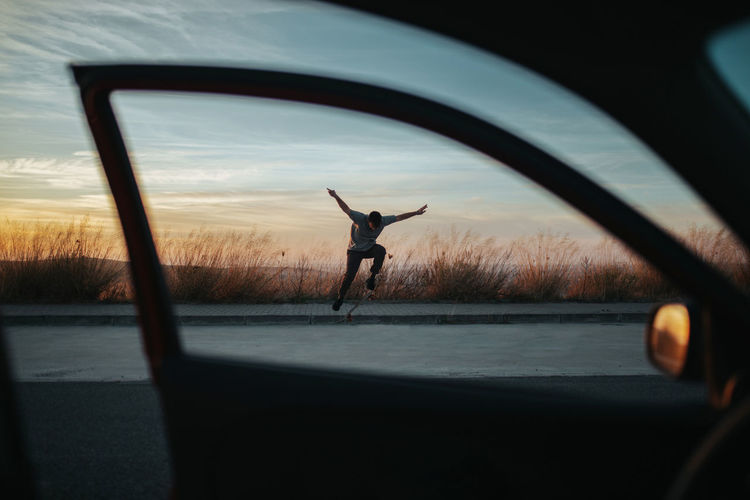 Silhouette man jumping on road against sky during sunset