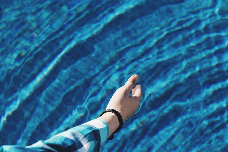 Cropped hand of man by swimming pool