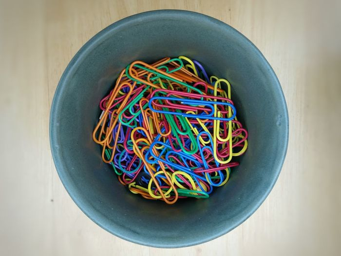 Directly above shot of paper clips in container on table
