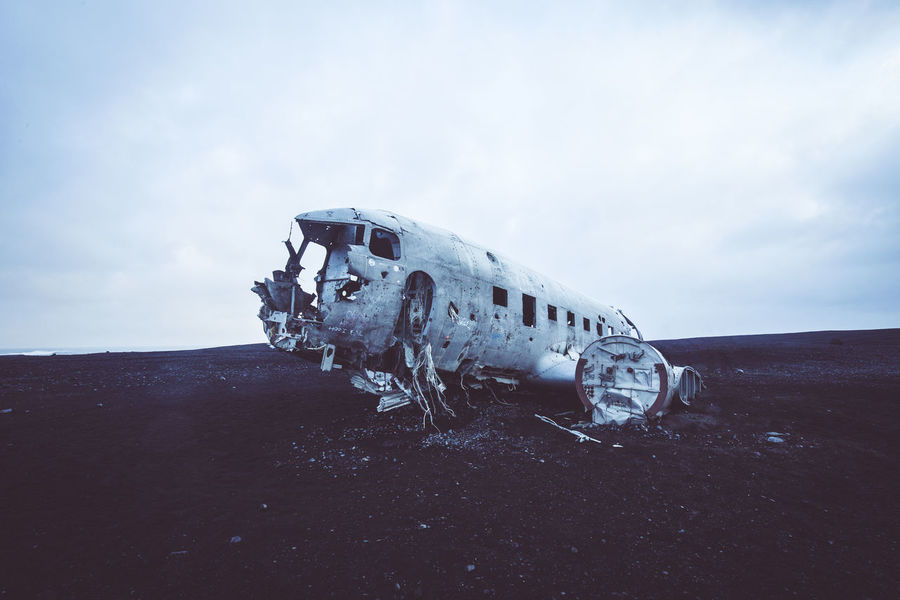 """Days of travel: 6 Sólheimasandur Plane Wreck On Saturday Nov 24 1973, the United States Navy airplane - a Douglas Super DC-3 - was forced to crash land on Sólheimasandur black-sand beach. The plane was falling over Vatnajökull, the largest glacier in Europe, and plummeting directly toward a jagged 5,000-foot peak. The main pilot put out a mayday and frantically tried to restart the engines. Just then, Lieutenant Gregory Fletcher, a 26-year-old pilot in training, grabbed the controls deciding to veer south and ditch the plane in the ocean. He knew that hypothermia would set in after about 15 seconds, but colliding with the icy crag would kill them all instantly. When the plane tore out of the clouds, Fletcher realized that they were gliding over """"some goddamn thing that looked like the moon."""" He lowered the plane parallel to the shore, used the frozen black-sand beach as a runway, and skidded 90 feet over a sand dune before slowing to a stop 20 feet from the ocean. The crew all survived the impact, but the plane was abandoned rather than recovered, meaning the weather-beaten remains are still standing at the crash site, deserted in a haunting, post-apocalyptic grave. The story behind its final descent has remained a mystery. No one seems to know why exactly this thing crashed, why it was abandoned, and why it's still lying on the beach. And even the date of the crash is shrouded in mystery - while the Aviation Safety Network reports that the airplane went down on November 24, an Icelandic newspaper suggests it actually crashed on November 21. Abandoned Places Crash Iceland Abandoned Air Vehicle Airplane Bad Condition Broken Cloud - Sky Cold Temperature Crash Damaged Demolished Deterioration Iceland Trip Iceland_collection Land Nature No People Obsolete Old Outdoors Ruined Run-down Travel Adventures In The City This Is My Skin The Great Outdoors - 2018 EyeEm Awards"""