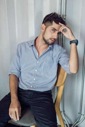 Portrait of young man sitting at home