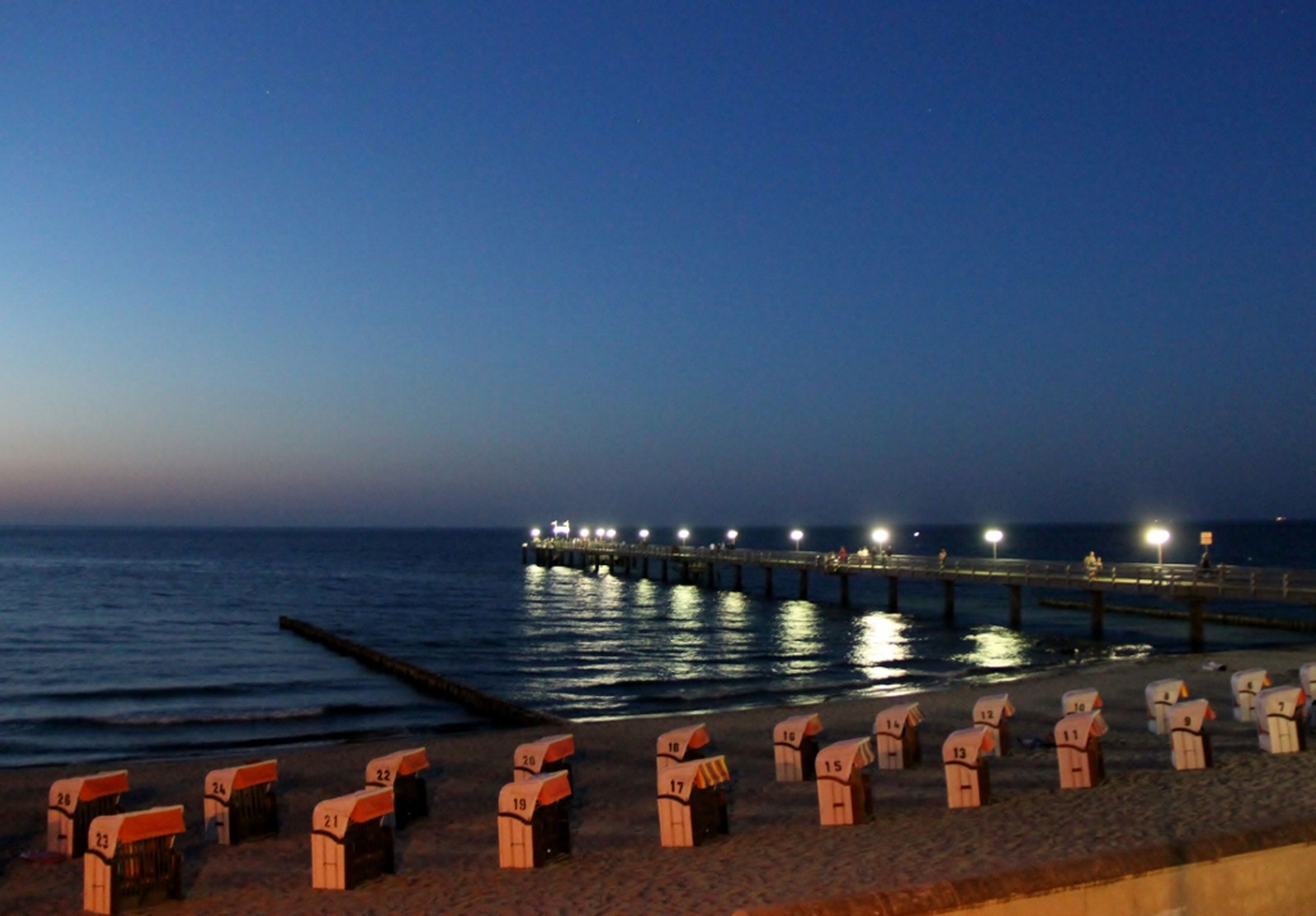 water, sea, copy space, clear sky, pier, tranquil scene, tranquility, scenics, horizon over water, railing, jetty, beauty in nature, nature, beach, illuminated, blue, idyllic, night, in a row, outdoors