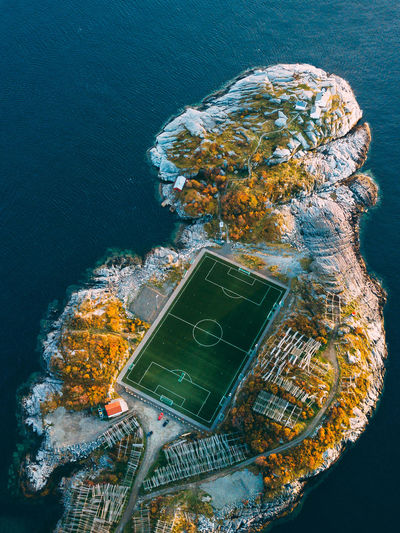 Aerial view of rock formation and soccer field against sea