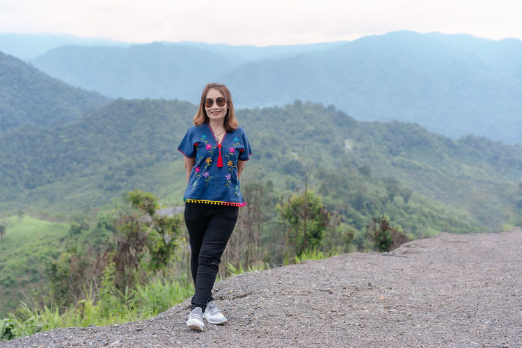 Adult traveling woman wearing sunglasses standing and smiling on the top of the mountain cliff