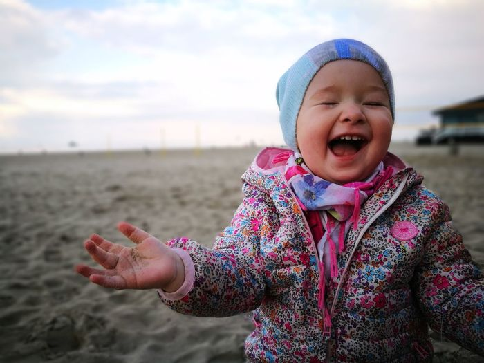 Human Body Part Childhood One Person Mouth Open Child Laughing People Smiling One Girl Only Outdoors Scarf Beach Children Only Day Girls Happiness Warm Clothing Portrait Cheerful Real People