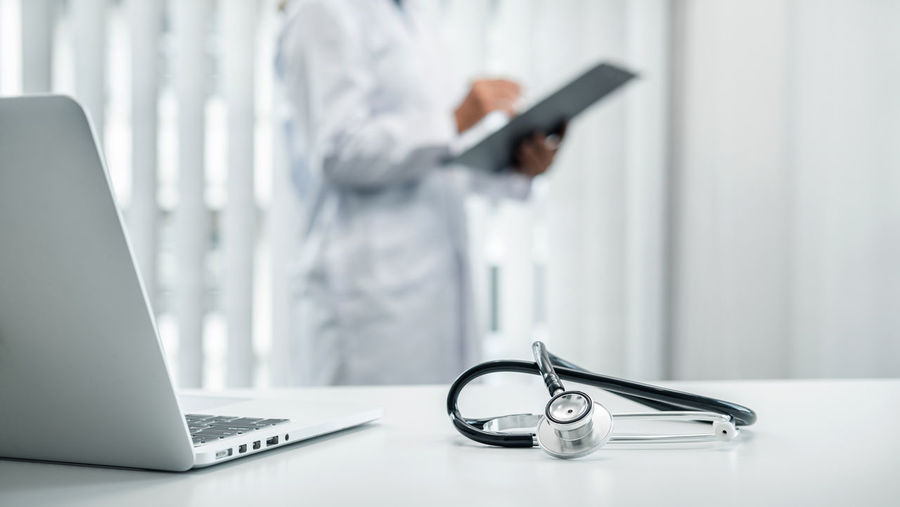 Midsection of doctor writing on clipboard