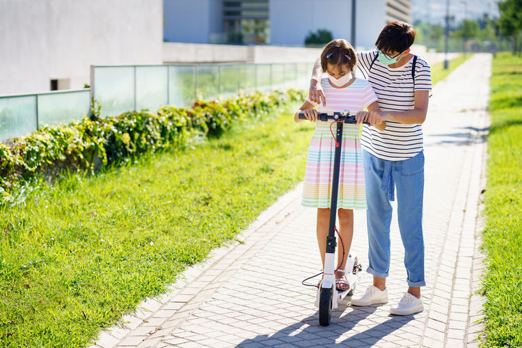 Full length of mother and daughter wearing mask standing on footpath