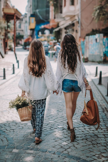 Two hippie friends woman walking on the street in the summer. friendship and freedom concept