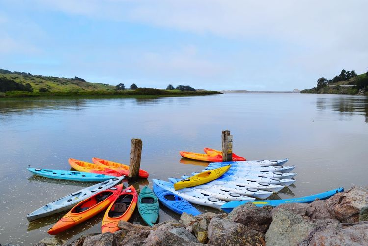 Kayaks moored on beach against sky