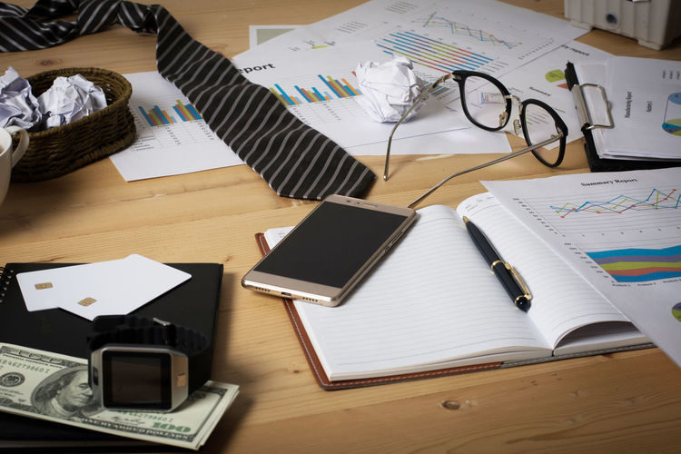 Book Business Communication Connection Desk Furniture High Angle View Indoors  No People Office Paper Pen Portable Information Device Publication Smart Phone Still Life Table Technology Wireless Technology Wood - Material