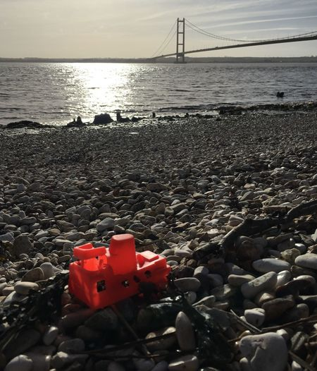 Hull City Of Culture 2017 Winter Sky River Humber Looking Over Water Suspension Bridge Humber Bridge Orange Boat Plastic Toy Driftwood Foreshore Pebbles And Stones Sun Reflection On Water