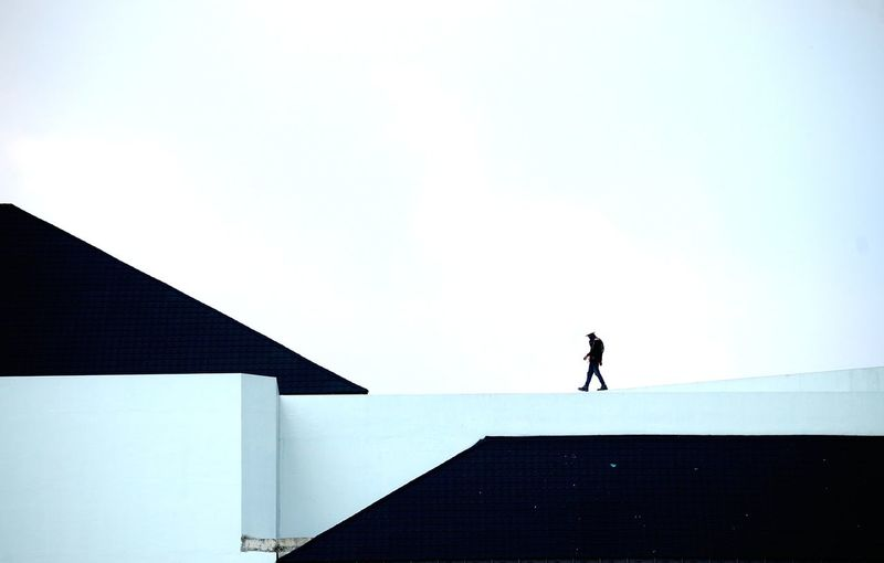 Silhouette man standing against clear sky, siluet worker up of building like on the mountain