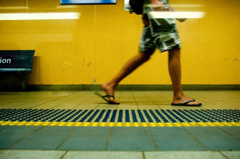 Low section of man walking on illuminated subway station