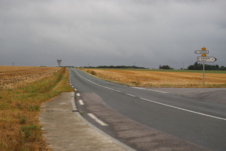 Road amidst cut cornfields against moody sky with water tower, saint vincent des bois, france