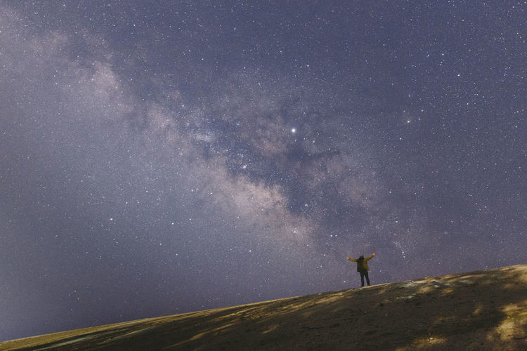 Silhouette man standing on field against star field in sky at night