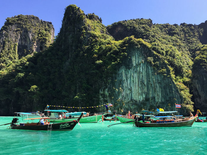Several tourist boats located in Maya Bay in Phi Phi Thailand. Thailand Travel Beauty In Nature Day Group Of People Mode Of Transportation Mountain Nature Nautical Vessel Outdoors Plant Rock Rock - Object Rock Formation Scenics - Nature Sea Sky Transportation Travel Tree Water Waterfront