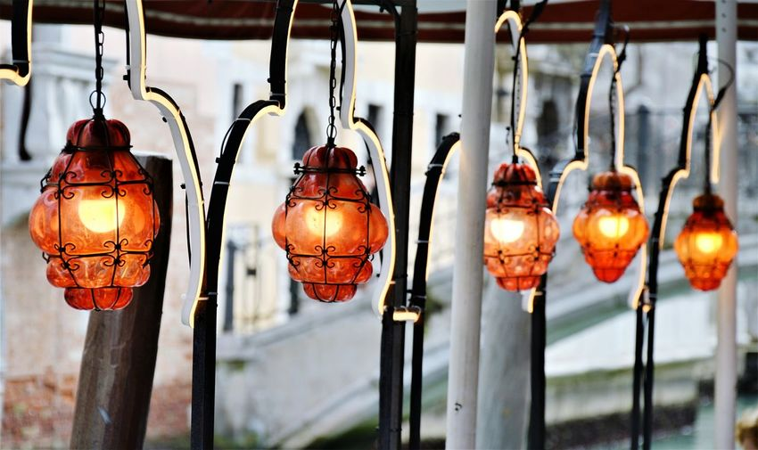 Close-up of illuminated lanterns hanging in row