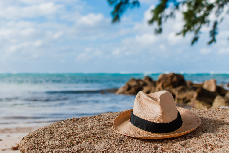 Straw hat in rum point beach overlooking the ocean