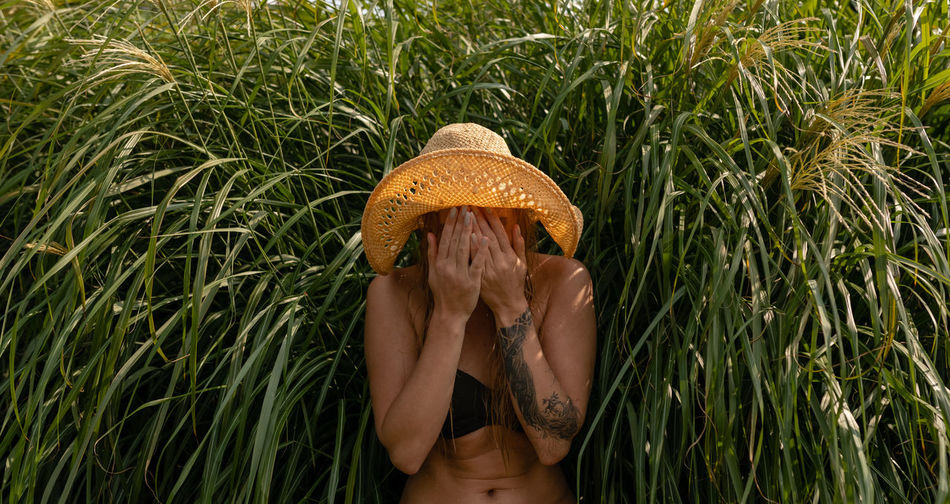 Young woman covering face while standing against plants