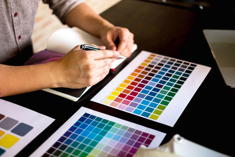 Midsection of businessman analyzing color swatches on table