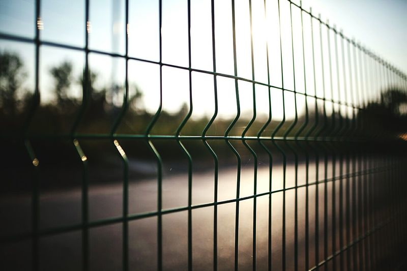 Close-Up Of Metal Fence By Road Against Clear Sky
