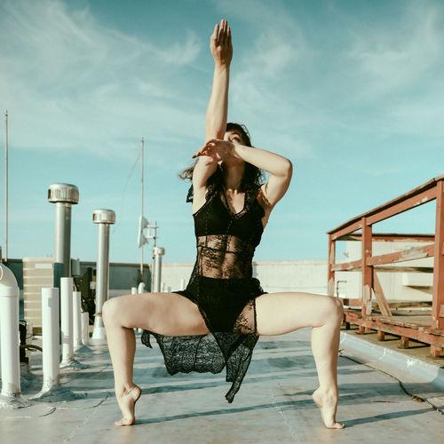 Full length of woman dancing against sky
