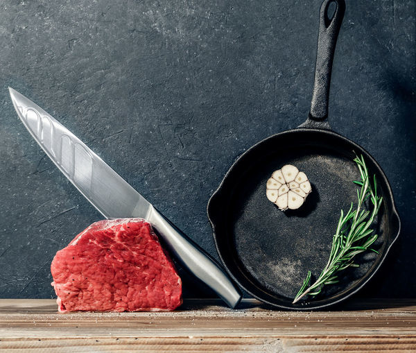 Close-Up Of Meat With Table Knife And Frying Pan
