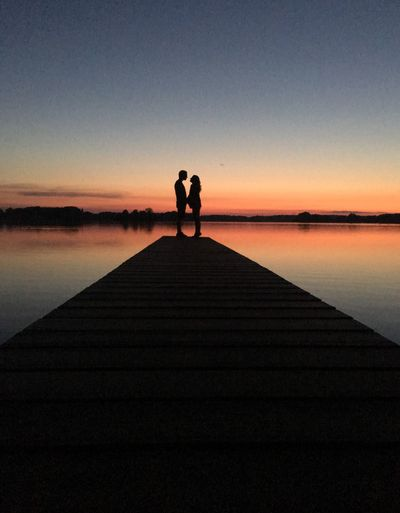 Mid distance view of silhouette couple standing on pier at lake against clear sky during sunset