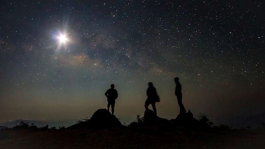 Silhouette men against sky at night