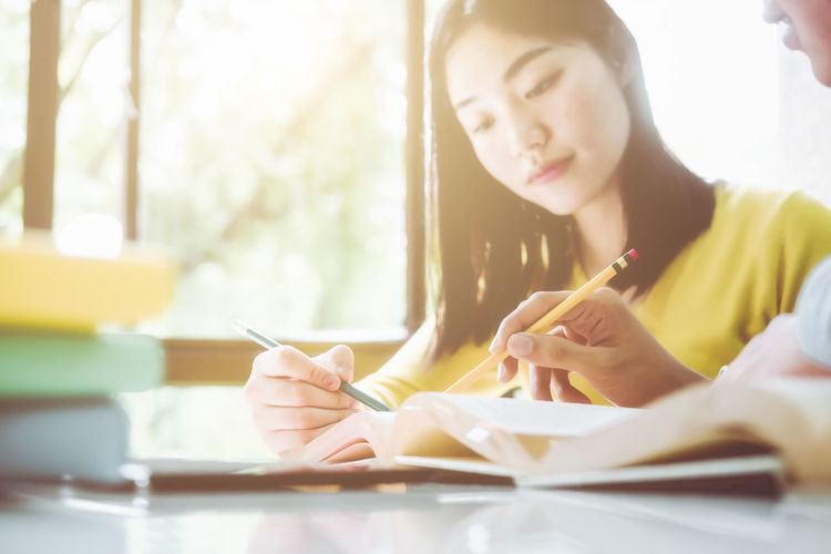Midsection of woman holding book while sitting on table