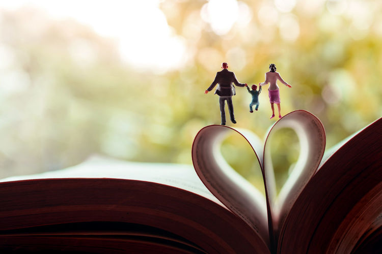 Love and Happy Family. Work Life Balance Concept. Miniature of Father, Mother and Son holding Hands and Walking toward the Book over a Page Roll like Heart Shape Love Family Happy Concept Miniature Heart Balance Work Child Healthy Day Hand Mother Kid Park Happiness Holiday People Holding Walking Woman Lifestyle Life Valentine Joy Together Boy Father Fun Children Figure Book Reading Fold Roll Shape Sign Symbol Closeup Macro Photo Mini Nobody Close-up Still Life Figurine  Emotion Nature
