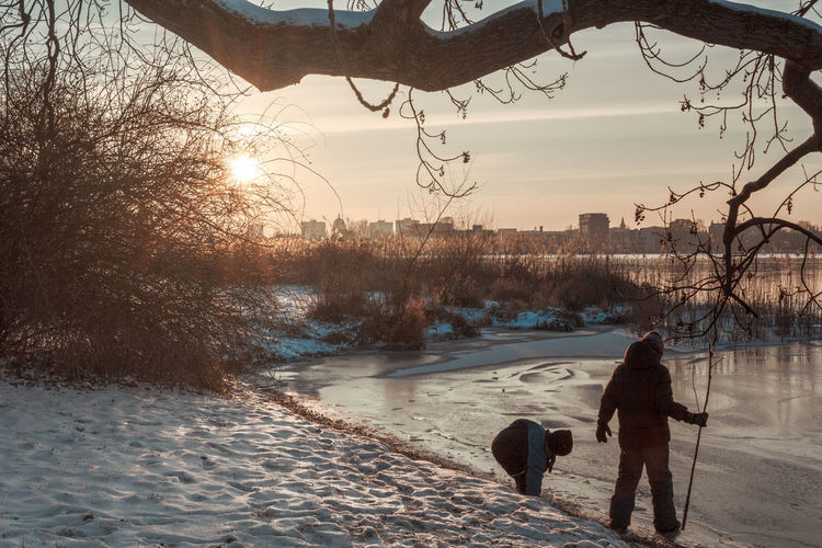 Children Bare Tree Brothers Childhood Cold Temperature Day Full Length Nature Outdoors Playing Real People Sky Snow Sunlight Sunset Winter Stories From The City