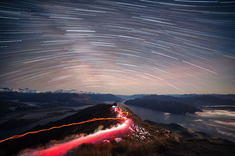Star trails over landscape against sky at night