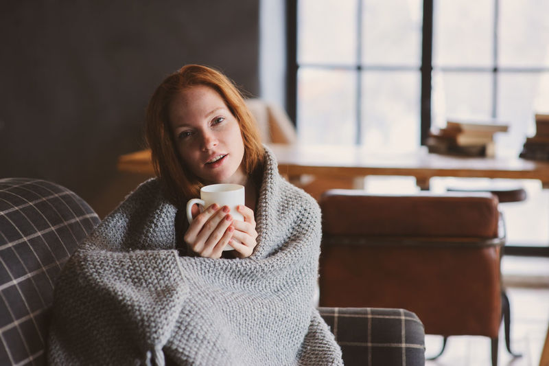 Portrait Of Young Woman Wrapped In Blanket Holding Coffee Cup On Sofa At Home