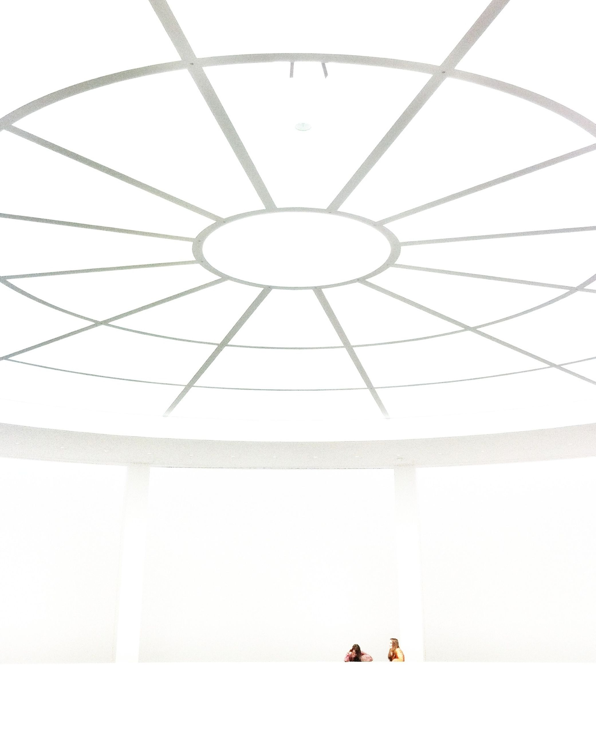 indoors, ceiling, lighting equipment, low angle view, wall - building feature, copy space, hanging, geometric shape, white color, circle, pattern, electric lamp, electricity, built structure, wall, no people, technology, architecture, electric light, modern