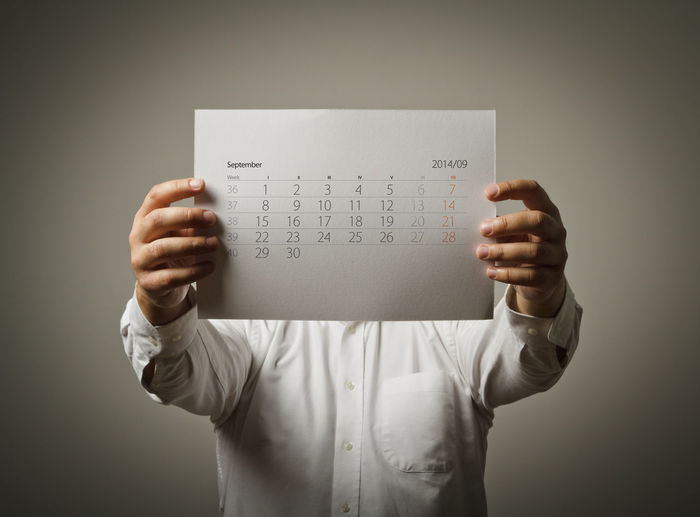 Man holding calendar in front of face while standing against gray background