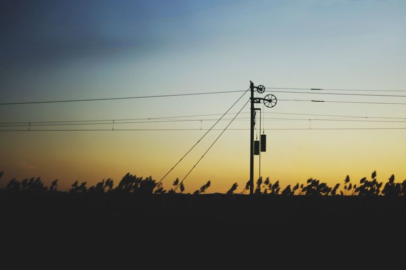 Silhouette of train electricity pylons against clear sky during sunset Energy Transportation Train Sky Sunset Silhouette Electricity  Cable Power Line  Technology Electricity Pylon No People Power Supply Fuel And Power Generation Outdoors Copy Space Clear Sky