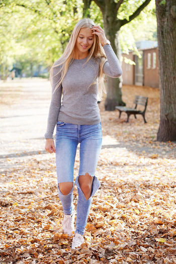 Blond Hair One Person Young Adult Beautiful Woman Portrait Girl Young Woman Women Teenager Teen Teenage Girls Real People People person Outdoors Outside Long Hair Casual Clothing Park Nature Day Sunny Sunny Day Spring Autumn Autumn Leaves Fall Walking Walk Full Length Happiness Smiling Jeans Candid