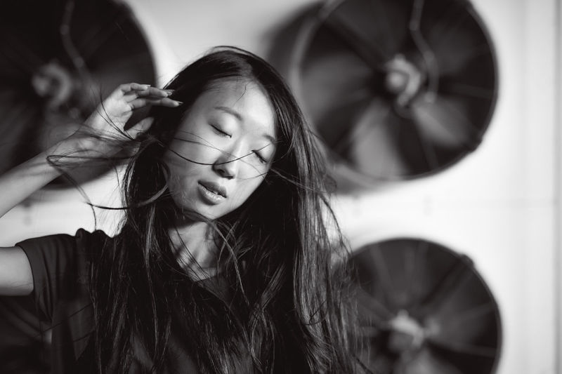 Young woman with tousled hair standing against exhaust fans