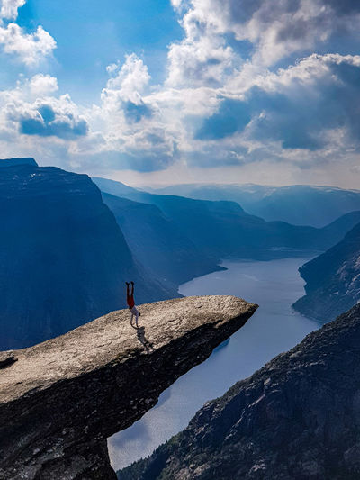High angle view of man doing handstand on rock by mountains against sky