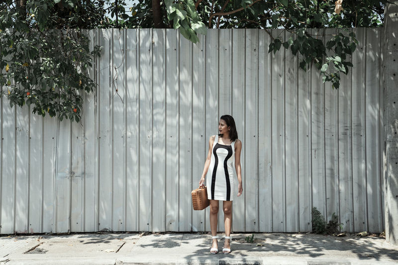 Full length of woman standing by wall outdoors