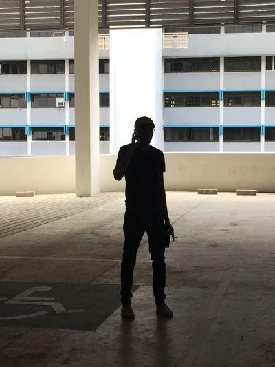Silhouette man talking on mobile phone while standing against building