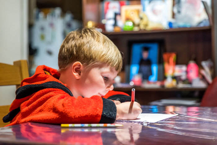 Boy writing letter to Santa Claus at table Workout Boys Childhood Day Education Headshot Home Indoors  Letter People Pijamas Real People Santa Claus Sitting Wish Writing